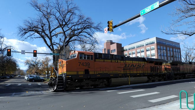 A train traveling the BNSF Railway tracks crosses Oak Street in Old Town Fort Collins, where city officials hope to establish a quiet zone where trains would no longer be required to sound their horns.