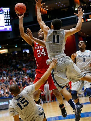 North Carolina State Wolfpack forward T.J. Warren (24) attempts to shoot past Xavier Musketeers guard Dee Davis (11) and guard Myles Davis (15) in the first half of a college basketball game during the first round of the 2014 NCAA Tournament at UD Arena.