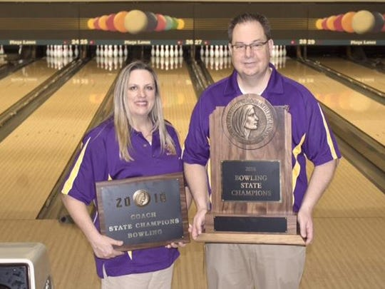 Johnston coach Xan Taylor holds her coach of the year plaque and coach Scott Taylor hold the state girls' bowling championship trophy.