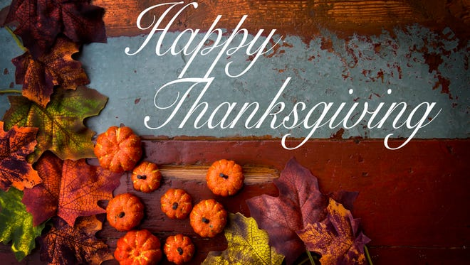 Happy Thanksgiving on wooden vintage board with pumpkins and leaves