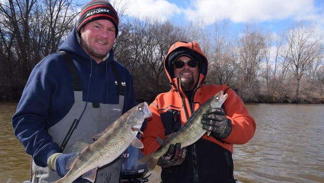 Brandon Stanton and Matt LaFond compare walleyes on the Saginaw River.