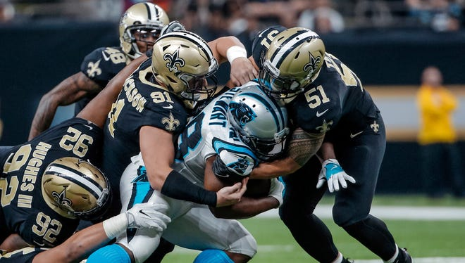 Carolina Panthers running back Jonathan Stewart (28) is stopped by the New Orleans Saints defensive players middle linebacker Manti Te'o (51) and defensive end Trey Hendrickson (91) and defensive tackle John Hughes (92) during the second quarter at the Mercedes-Benz Superdome.