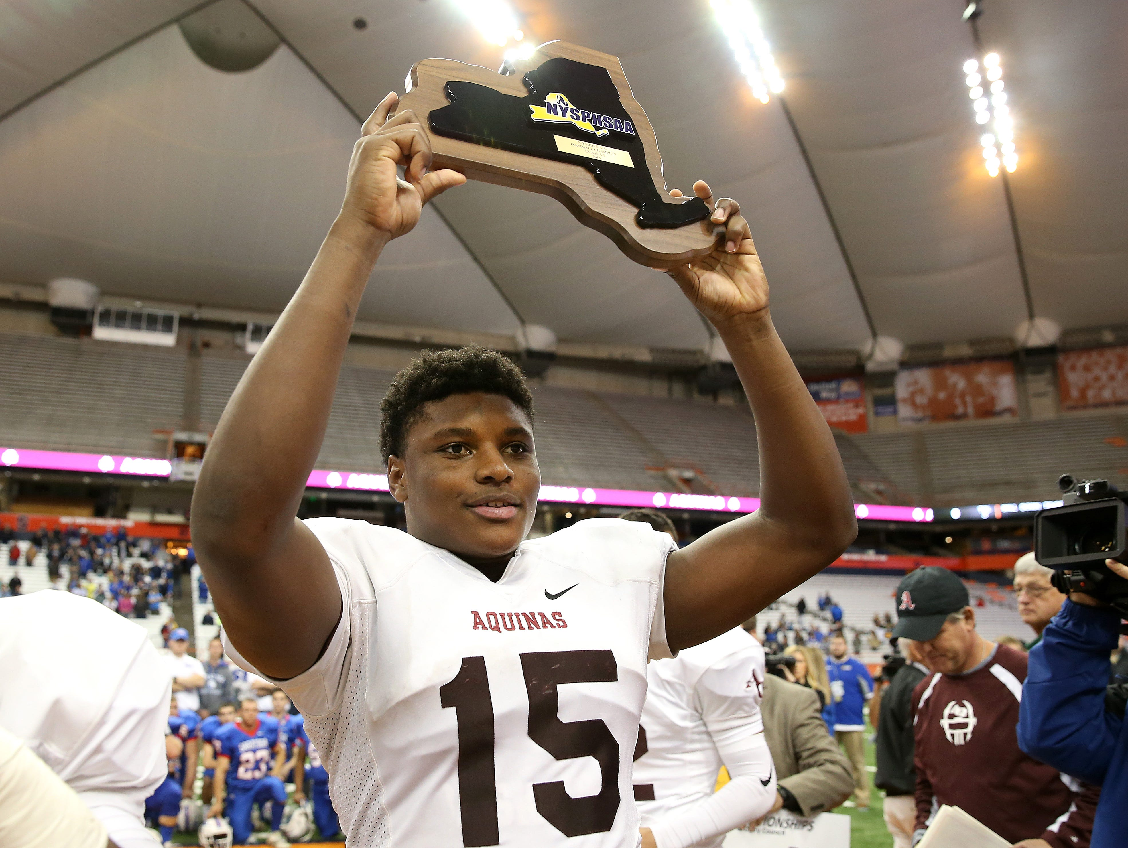 Aquinas' Jamir Jones holds up the championship plaque after Aquinas defeated Saratoga Springs 44-19 to win the state Class AA title on Sunday.