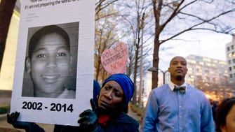 Tomiko Shine holds up a picture Dec. 1, 2014, of Tamir Rice, the 12-year-old boy fatally shot Nov. 22 by a rookie Cleveland police officer.