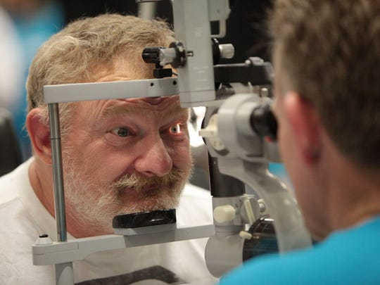 Rex King has his eyes checked by David Pierce during a 2014 Hope Connection event.