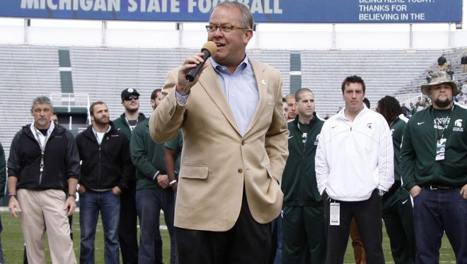 FILE - In this April 26, 2014, file photo, Michigan State athletic director Mark Hollis introduces members of the 2013 Big Ten Championship and 2014 Rose Bowl Championship team during halftime of an NCAA college spring football scrimmage in East Lansing, Mich. Michigan State athletic director Mark Hollis will be the vice chairman of the NCAA Division I men's basketball committee this season and lead the selection of the field of 68 for the 2016-17 season. The NCAA named Hollis to the position on Tuesday, July 21, 2015. (AP Photo/Al Goldis, File)