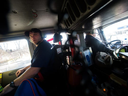 Bloomfield Fire Department volunteer firefighter Chris Warner, left, rides on Friday with firefighter engineer Ryan Varnell in the station's fire truck on the way to a safety inspection site in Bloomfield.