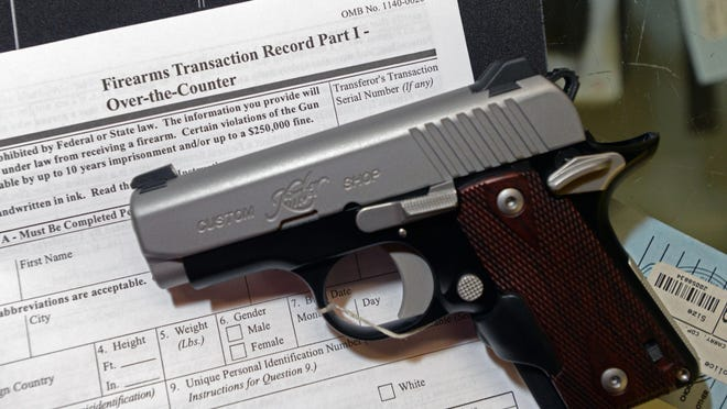 A handgun rests on form 4473, which is required for a background check and purchase of a gun.