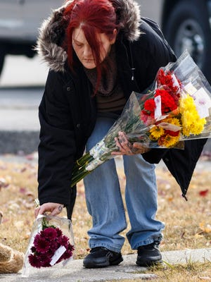 Michelle Hutto brings flowers to a makeshift memorial at Woodmore Elementary on Tuesday, Nov. 22, 2016, in Chattanooga, Tenn. A Monday afternoon school bus crash killed at least 5 elementary schoolchildren that attended Woodmore.  (Doug Strickland/Chattanooga Times Free Press via AP)