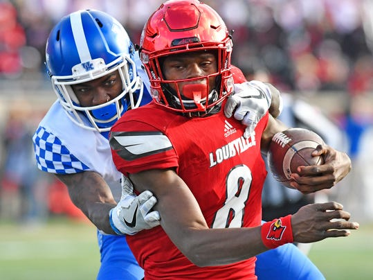 Louisville quarterback Lamar Jackson (8) is dragged down from behind by Kentucky's J.D. Harmon (11) during the second half of an NCAA college football game, Saturday, Nov. 26, 2016, in Louisville, Ky. Kentucky won 41-38. (AP Photo/Timothy D. Easley)
