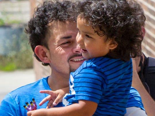 Ever Reyes Mejía estrecha en sus brazos a su hijo de 3 años luego que autoridades de EU se lo entregaran el martes 10 de julio, 2018.
