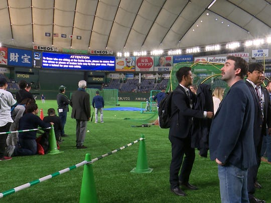"""In this Thursday, March 21, 2019, image from video, Joey Mellows from Portsmouth, England, looks at the spectators' stand during  the Seattle Mariners' batting practice before Game 2 of the Major League Baseball opening series between the Mariners and the Oakland Athletics at Tokyo Dome in Tokyo. Mellows, better known by his Twitter feed """"Baseball Brit,"""" has quit his job to watch an entire season of Major League Baseball games. Some may see it as a frivolous pursuit but others are impressed by his free spirit. (SNTV via AP)"""