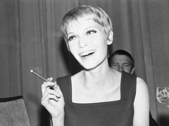 Cigar-smoking Mia Farrow, wife of American singer Frank Sinatra, is shown in her hotel room in Berlin, during a news conference, April 20, 1967.