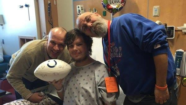 IndyStar columnist Gregg Doyel (left) visits with Noah Holland and his dad, Chad, at Riley Hospital for Children.