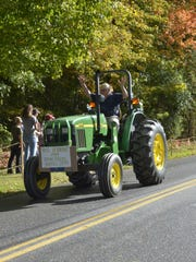 A participant in the annual East Charlotte Tractor Parade raises his arms as he rides down Spear Street on Sunday, Oct. 8, 2017.