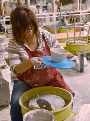 Charleen Beard removes her piece from the potter's
