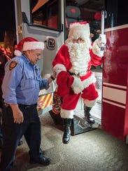 Capt. Jim Davison helps Santa Claus make his big arrival