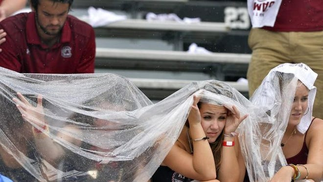 USC Gamecocks fans try to stay dry in the stands before the Georgia Bulldogs game at Williams-Brice Stadium in Columbia on Saturday, September 13, 2014.