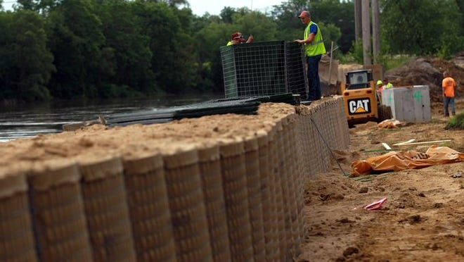 HESCO barriers are raised along the Iowa River at the Cole Mobile Home Park on Wednesday, July 2, 2014.
