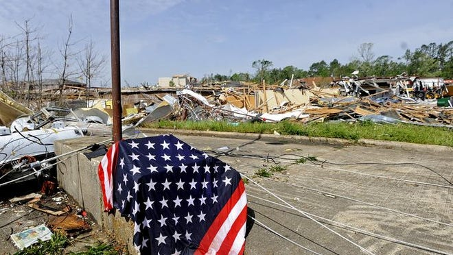 An American flag rests on a pillar as damaged buildings are seen in the background on North Gloster Street in Tupelo, Miss., Tuesday, April 29, 2014.