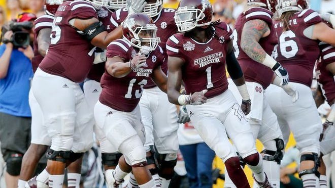 Mississippi State Bulldogs wide receiver De'Runnya Wilson (1) celebrates with teammates after scoring a touchdown against the LSU Tigers during the first quarter of a game at Tiger Stadium.
