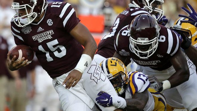 Mississippi State quarterback Dak Prescott (15) is sacked for a loss by LSU cornerback Dwayne Thomas (13) in the first half of an NCAA college football game in Baton Rouge, La., Saturday, Sept. 20, 2014.