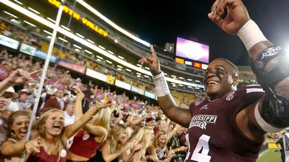 Christian Holmes celebrates with fans after Mississippi State's win at LSU.