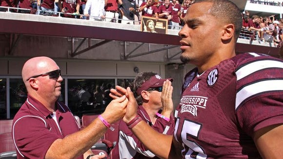 Mississippi State quarterback Dak Prescott (15), is congratulated after MSU defeated No. 5 Texas A&M 48-31 in an NCAA college football game in Starkville, Miss., Saturday, Oct. 4, 2014. (AP Photo/Jim Lytle)