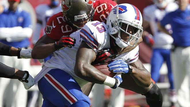 Buffalo Bills wide receiver Steve Johnson (13) runs with the ball as Tampa Bay Buccaneers cornerback Leonard Johnson (29) tackles during the first half at Raymond James Stadium.