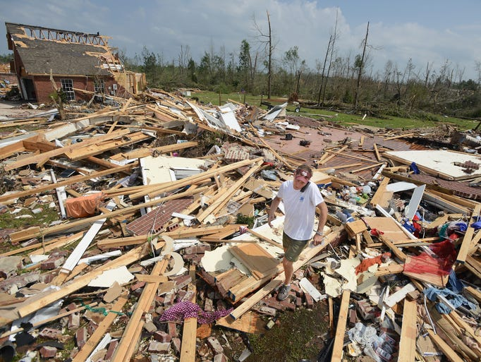 Jason Bane searches for personal items the the rubble of a home on Wood Street in northeast Louisville on Tuesday while on the phone with the home's owner who was in the home with his family when a powerful tornado ripped through the area on Monday.  The occupants were pulled from the wreckage, injured but alive.