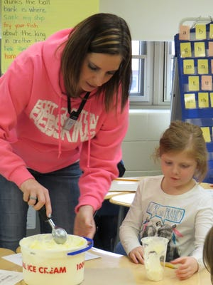 Bataan Memorial School first grader Kerigan Collins inspects her glass as teacher Christie Miller scoops ice cream in preparation for a lesson on solids, liquids and gas.