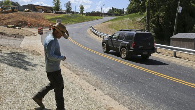 Union Chapel Road at Alabama Highway 69 in Northport was reopened Thursday, July 23, 2020, with a new traffic configuration that removed one of the two traffic signals from Highway 69, creating a single intersection. Ryan Elmore checks a blanket of straw placed on the shoulder to help grow grass as a motorist moves along the street behind him.