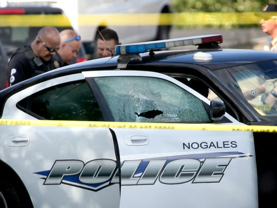 Law enforcement personnel near the bullet-proof patrol