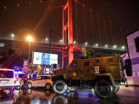 FILE - In this Sunday, Jan. 1, 2017 file photo, a police armoured vehicle blocks the road leading to the scene of an attack in Istanbul. Survivors of the massacre at a Turkish nightclub describe an hour of pure terror and how they escaped, by feigning death, rappelling to the sea, or hiding anywhere they could find. The Islamic State gunman fired 180 rounds for seven minutes, killing 39 people on New Year's Eve. He escaped after he wiped his Kalashnikov free of fingerprints, changed clothes, put on a Santa hat and blended into the crowd evacuating the bloody Reina nightclub.