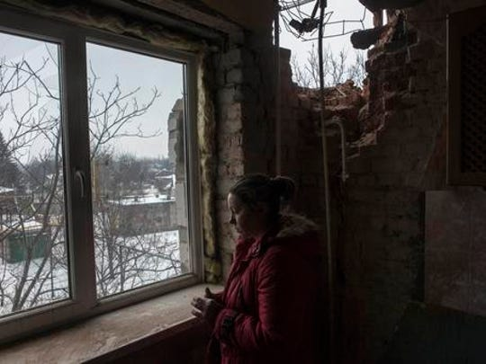 Olga Duzhikova looks through the window of her flat damaged by shelling in Avdiivka, Ukraine, Saturday, Feb. 4, 2017. Fighting in eastern Ukraine sharply escalated this week. Ukraine's military said several soldiers were killed over the past day in shelling in eastern Ukraine, where fighting has escalated over the past week.