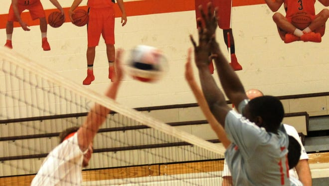 Princeton High School's Jamal Hines (14) blocks a spike attempt.