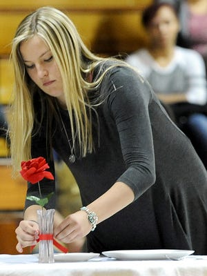 Senior Rachel Dane ties a ribbon on a vase during the P.O.W. and M.I.A. table ceremony.