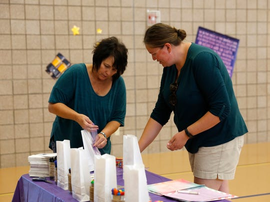 Sheridy Walker, left, and Virginia Weaver work on decorations for a dinner to honor cancer survivors on Thursday at the First Baptist Church in Bloomfield.