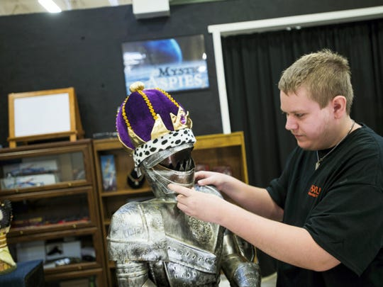 Tyler Mudgett, of Littlestown, adjusts a tin knight in armor at his store booth at the Markets at Hanover on Broadway on Oct. 22 in Hanover. Mudgett, who's in the spectrum for Autism, gets support and help from Focus Foundation.