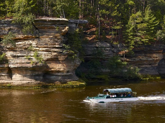 An Original Wisconsin Duck cruises past sandstone cliffs along the Wisconsin River in the Dells.