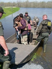 LDWF enforcement agents rescue a resident in a wheelchair in Natchitoches Parish.
