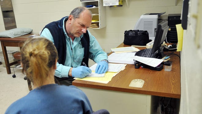 Dr. Thomas R. Vajen examines an inmate at the Fairfield County Minimum Security Jail in this Oct. 2008 file photo. Vajen is retiring as the medical director for the county jail and as the county coroner.