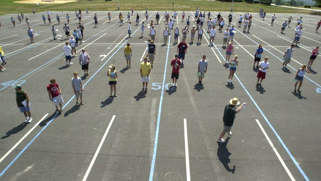 Dallastown Area High School band director James Dougert guides the Wildcat band into formation during preseason practice in the high school parking lot in this file photo.