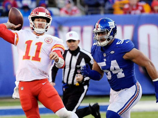 FILE - In this Sunday, Nov. 19, 2017, file photo, Kansas City Chiefs quarterback Alex Smith (11) throws a pass away from New York Giants' Olivier Vernon (54) during the second half of an NFL football game in East Rutherford, N.J. The Bills and Chiefs have been riding a similar rollercoaster this season. They both started hot behind great play at quarterback, and they both have stumbled as their QB play has suffered. Throw in similar injuries and you get two teams trying to right their season when they meet Sunday at Arrowhead Stadium.(AP Photo/Bill Kostroun, File)