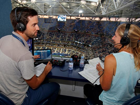 In this Monday, Sept. 5, 2016 photo, U.S. Open Radio broadcasters Brian Clark, left, and Jill Craybas talk during the fourth round of the tennis tournament in New York. Nearly 400 organizations from around the world are covering this year's U.S. Open, yet only two outlets, the BBC and U.S. Open Radio, call matches just for the ear.  (AP Photo/Adam Hunger)