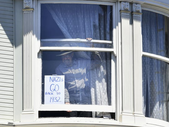 A man posts a sign in his window in San Francisco,