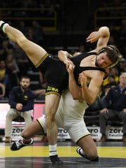 Iowa's Jaren Glosser wrestles Michigan's Alex Pantaleo at 157 pounds during the Hawkeyes regular-season meet against Michigan at Carver-Hawkeye Arena in Iowa City on Saturday, January 27, 2018. Iowa's usual starter at 157-pounds, Michael Kemerer, sat on the sideline on Saturday with an injury, (Ben Roberts/Freelance)