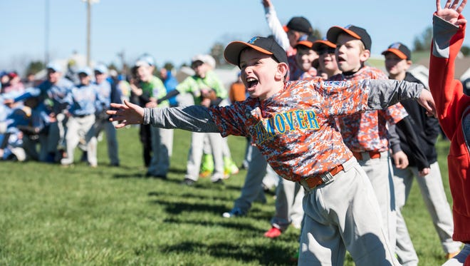 Hanover Little League players hand out high-fives during opening day ceremonies in April. On Tuesday, the HLL board voted to end its charter association with Little League International.