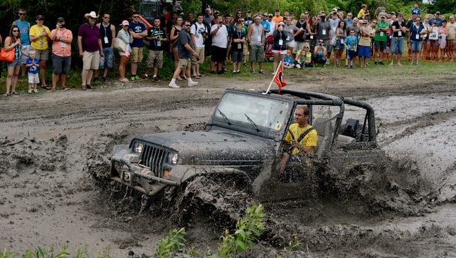 Jeep fans watch as a Jeep Jam participant makes his way through the mud pit in Berlin during the 5th annual Ocean City Jeep Week.