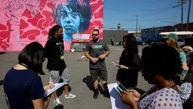 Murals in the Market co-founder Jesse Cory (center) talks to attendees at the 2017 festival.